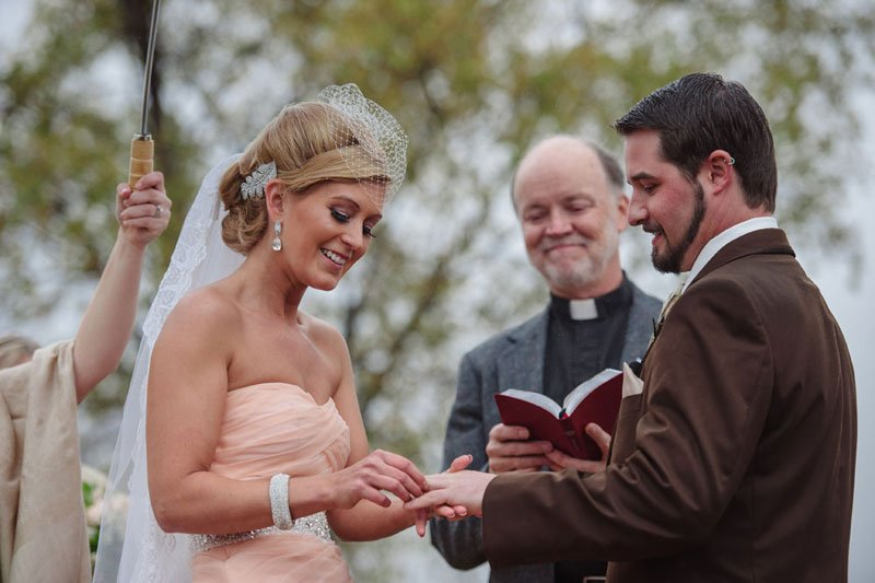 bride in pink ruffled dress puts ring on groom's finger for stillwater mn wedding