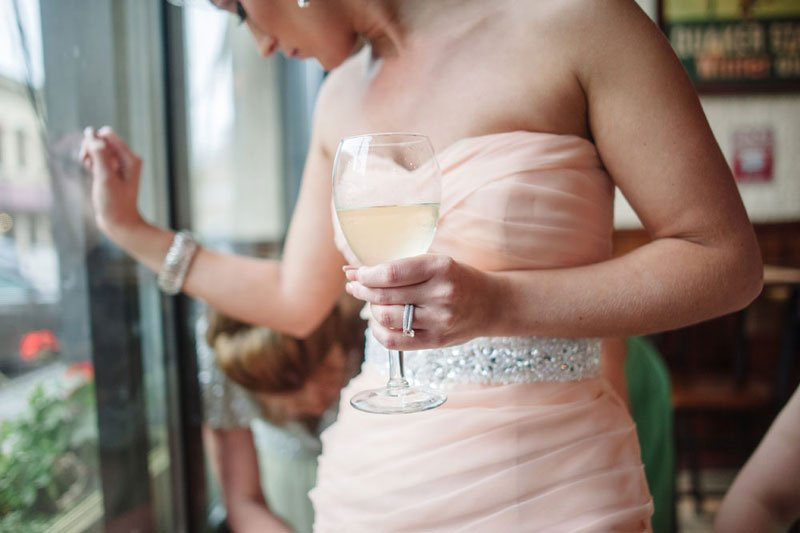 details of bride's pink ruffled dress with wine glass stillwater mn