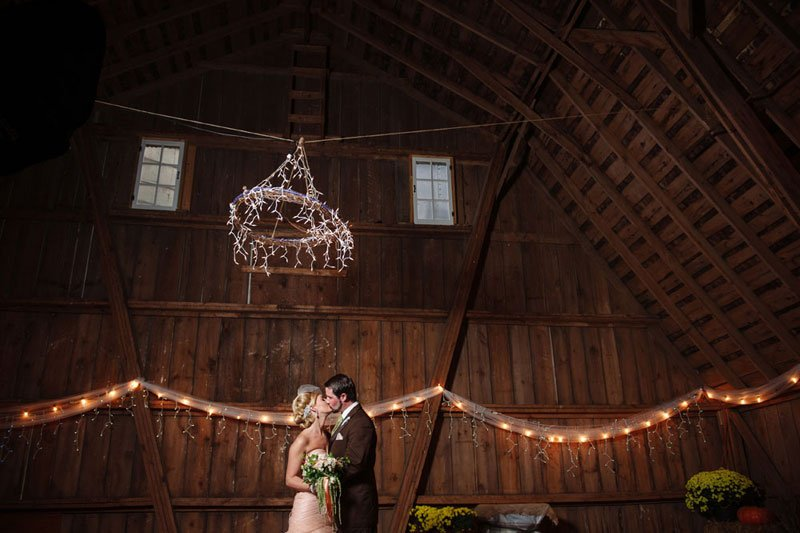 groom kisses bride in barn in WI