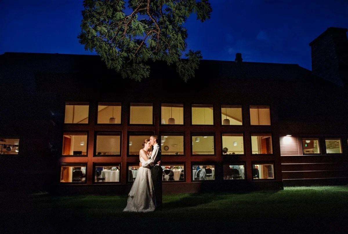 bride and groom at the end of the night with blue night sky with windows of dakota lodge behind them
