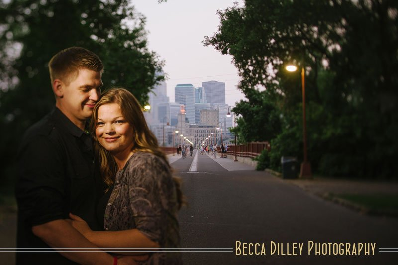 couple cuddled up at night with stone arch bridge in the background