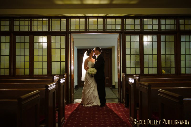 bride and groom by wall of windows at Bethlehem Lutheran Church wedding minneapolis mn