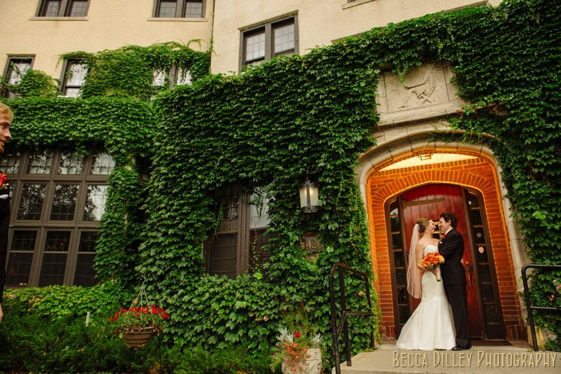 bride and groom under arch of st paul university club with warm backlight