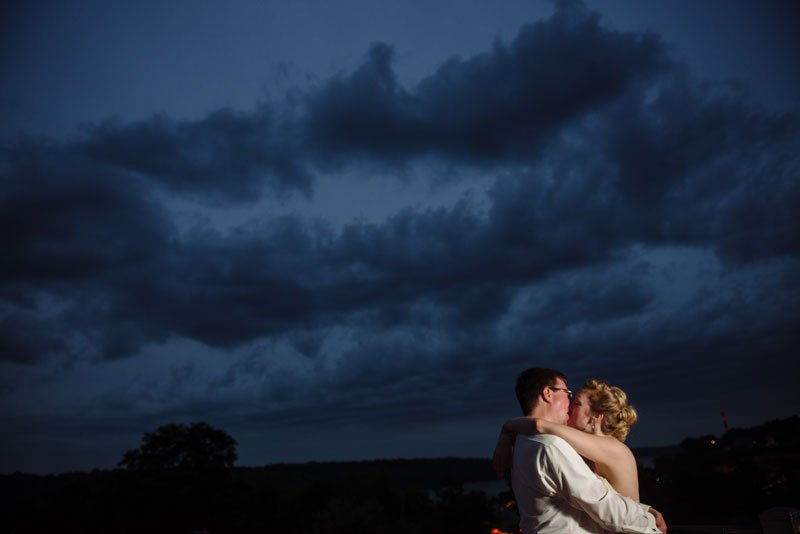 bride and groom kiss at night with clouds behind them