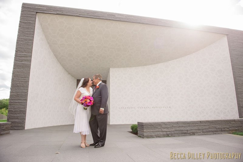 bride and groom in front of large modern white building at lakewood chapel minneapolis