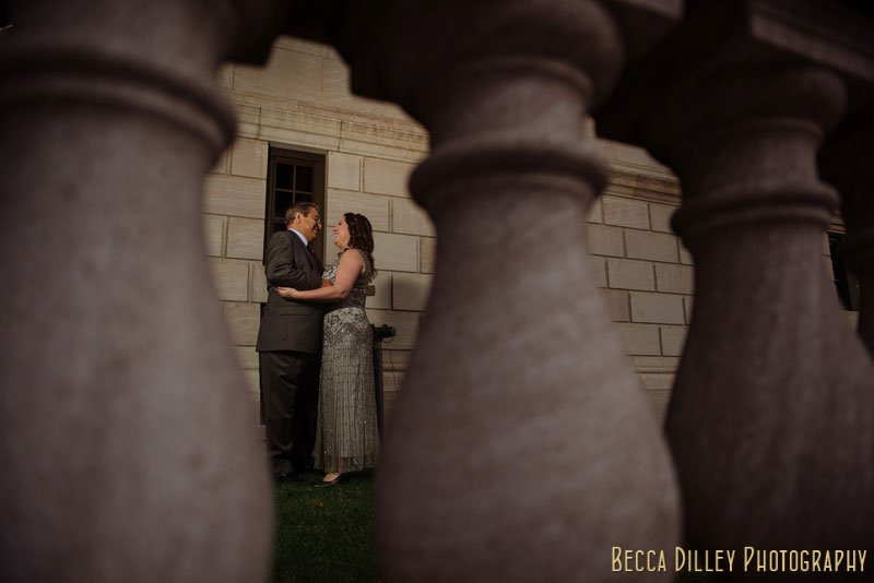 bride in silver dress with groom between columns of jj hill library