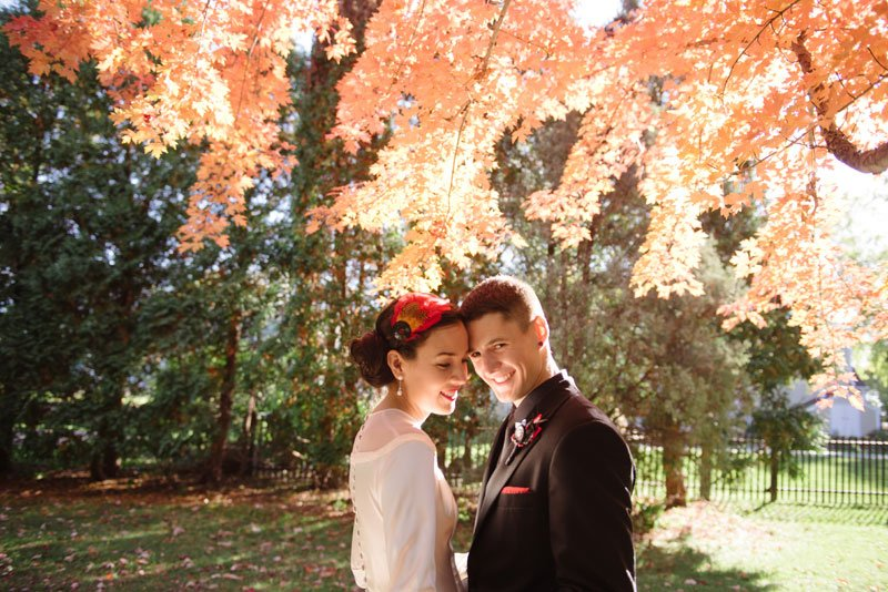 quiet moment of bride and groom under feathery orange leaves