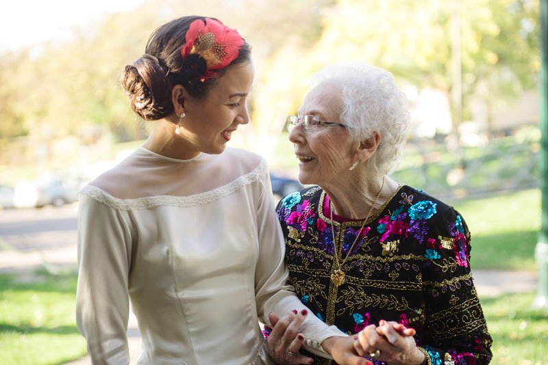 bride wearing grandmothers dress talks with grandma