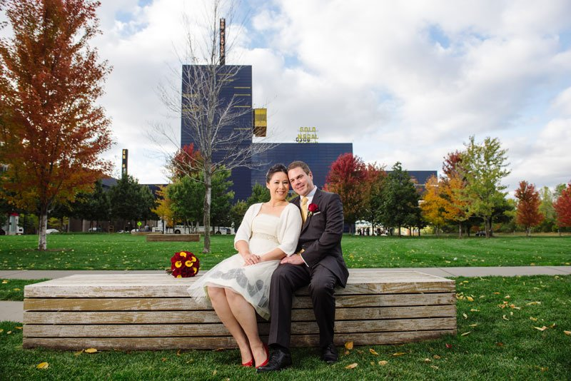 bride and groom in gold medal park with guthrie theater behind them