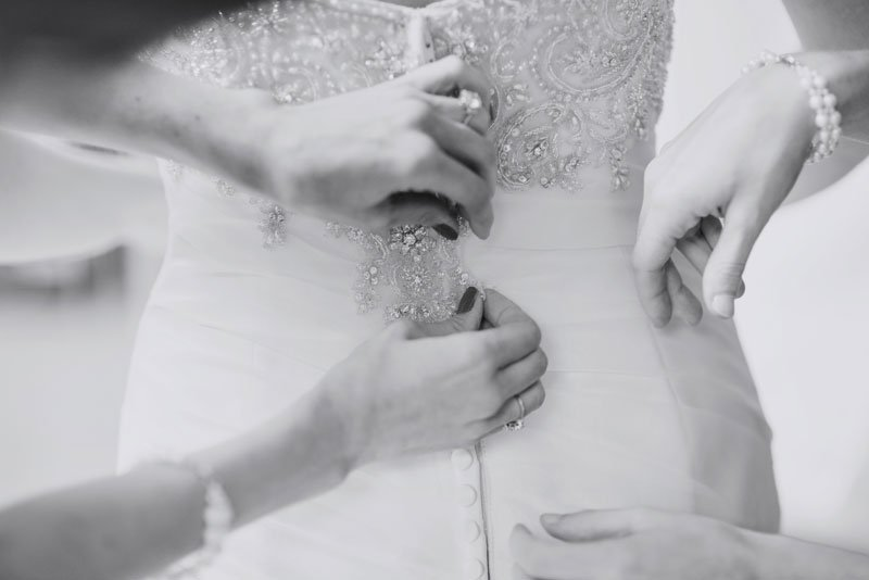wedding dress with lace details being buttoned