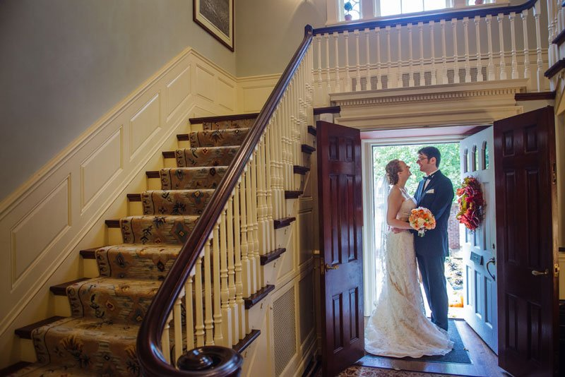 bride and groom with colonial staircase outside macalester college