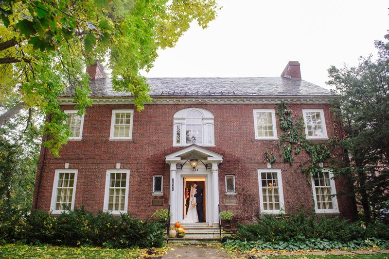 bride and groom in entry of alumni house before macalester college wedding