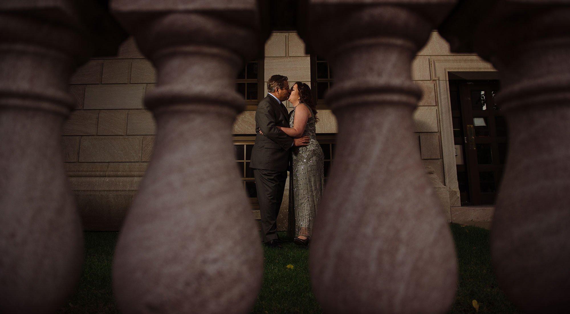couple in rice park for wedding photos between pillars