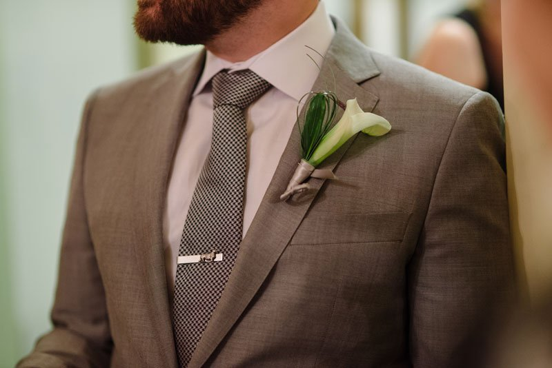 groom with checked tie and cala lilly boutonniere st paul college club wedding mn
