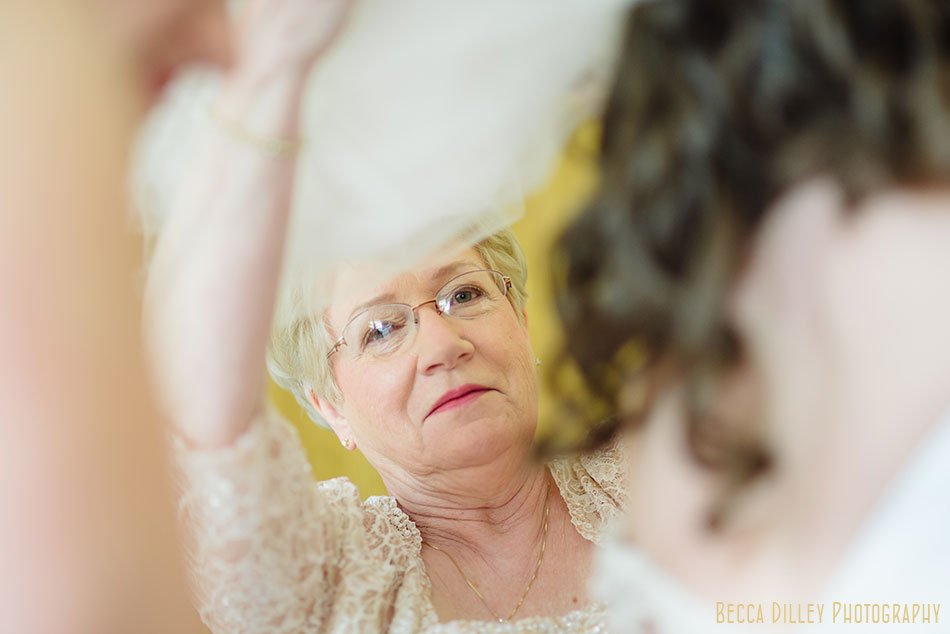 brides mom lifts veil while getting ready at St Maria Goretti church wedding madison wi