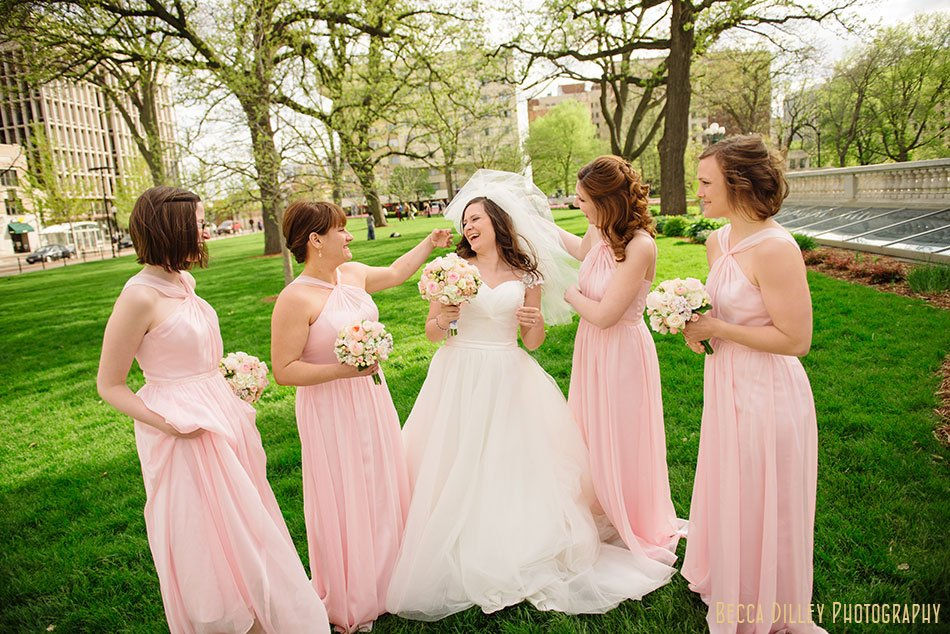 bride and bridesmaids in pink dresses laughing on lawn of madison capitol