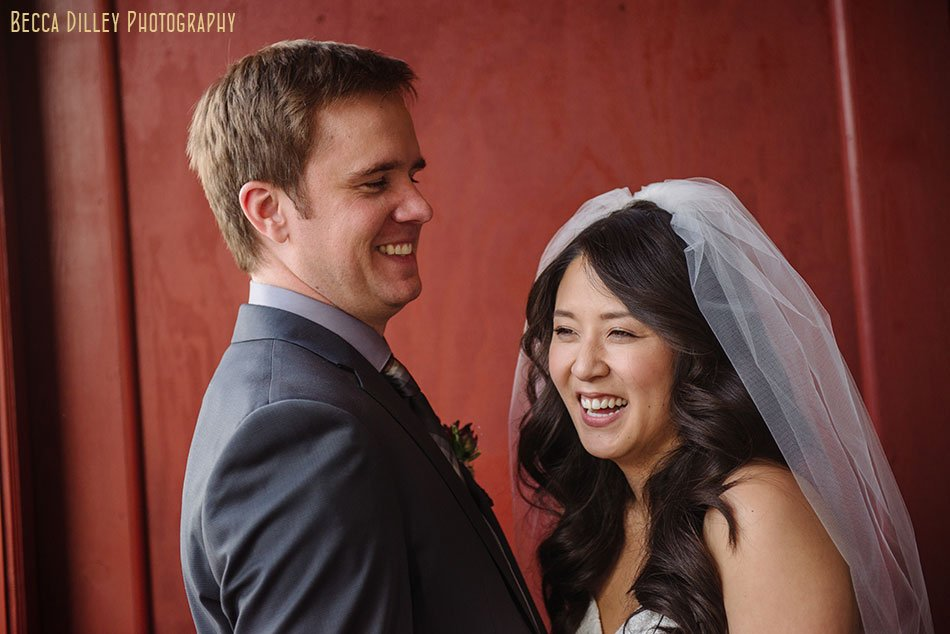 bride and groom with red wall of Loring Pasta Bar Minneapolis wedding