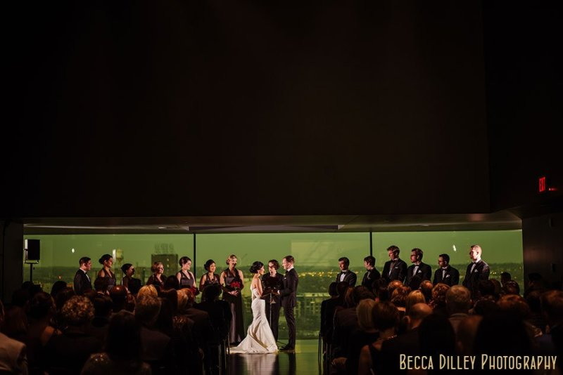 wedding ceremony in the guthrie theater's amber box room with a view of the mississippi river