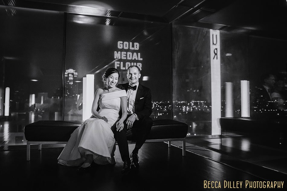 bride and groom sit on chair with guthrie theater marquee behind them