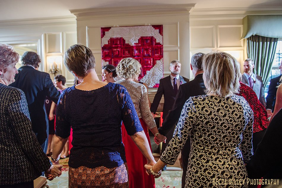 guests hold hand during ceremony st paul college club winter wedding mn
