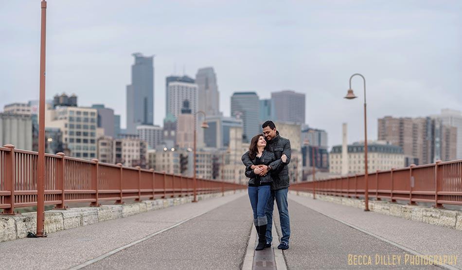 skyline minneapolis wedding photographer engagement photos at stone arch bridge in winter