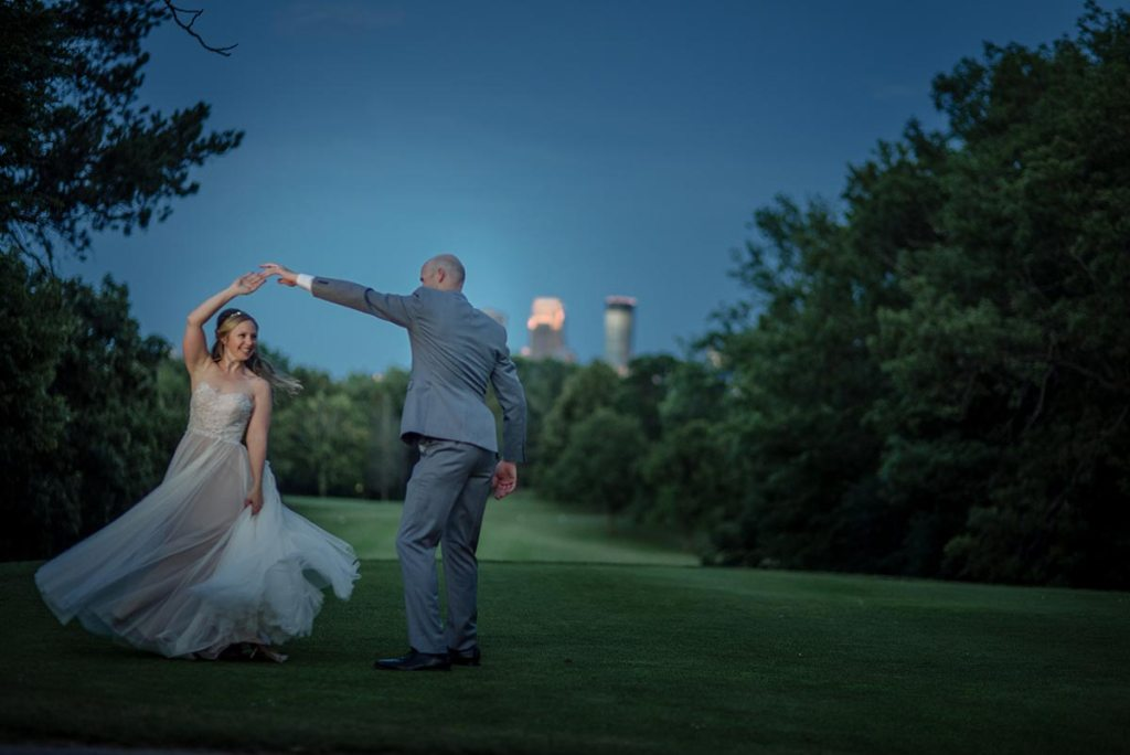 couple dancing in with the skyline behind them at night Theodore Wirth Chalet Wedding