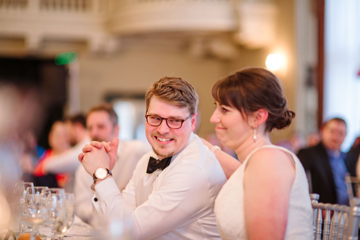 bride and groom laugh listenting to toasts at st paul athletic club wedding reception in grand ballroom
