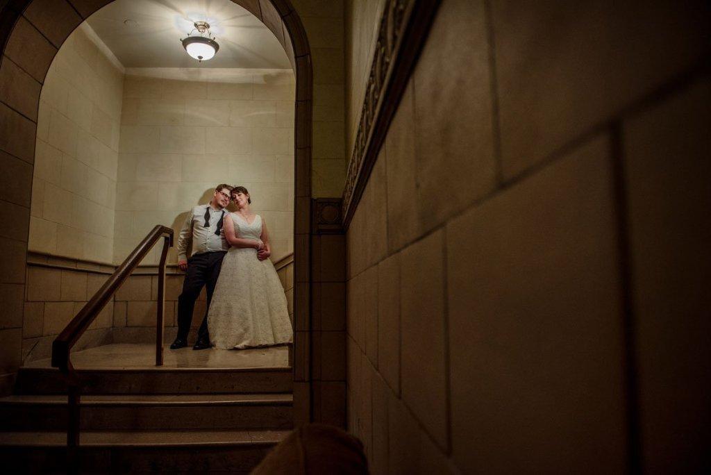 bride and groom under arches of lobby in st paul athletic club wedding minnesota best wedding photogtapher