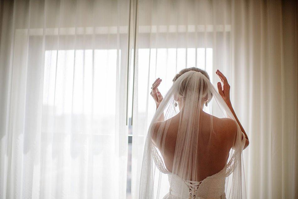Bride putting in veil, Minneapolis, MN