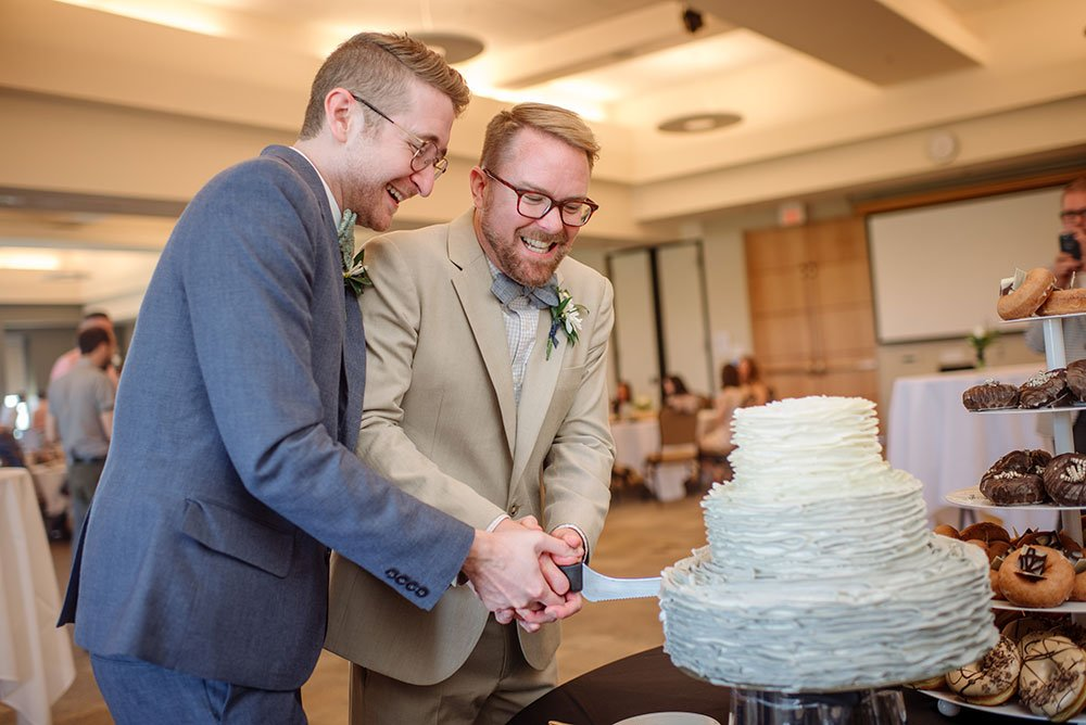 two grooms cut cake at St Olaf College Wedding