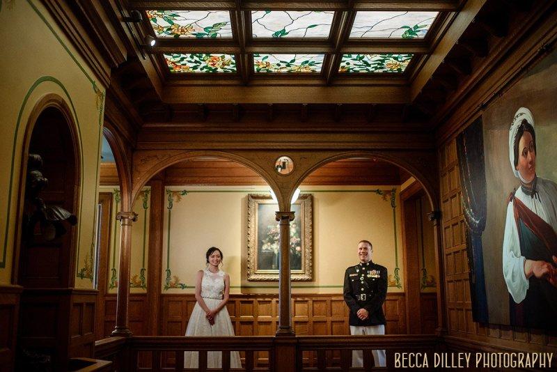 couple pose under arches inside Van Dusen Mansion minneapolis