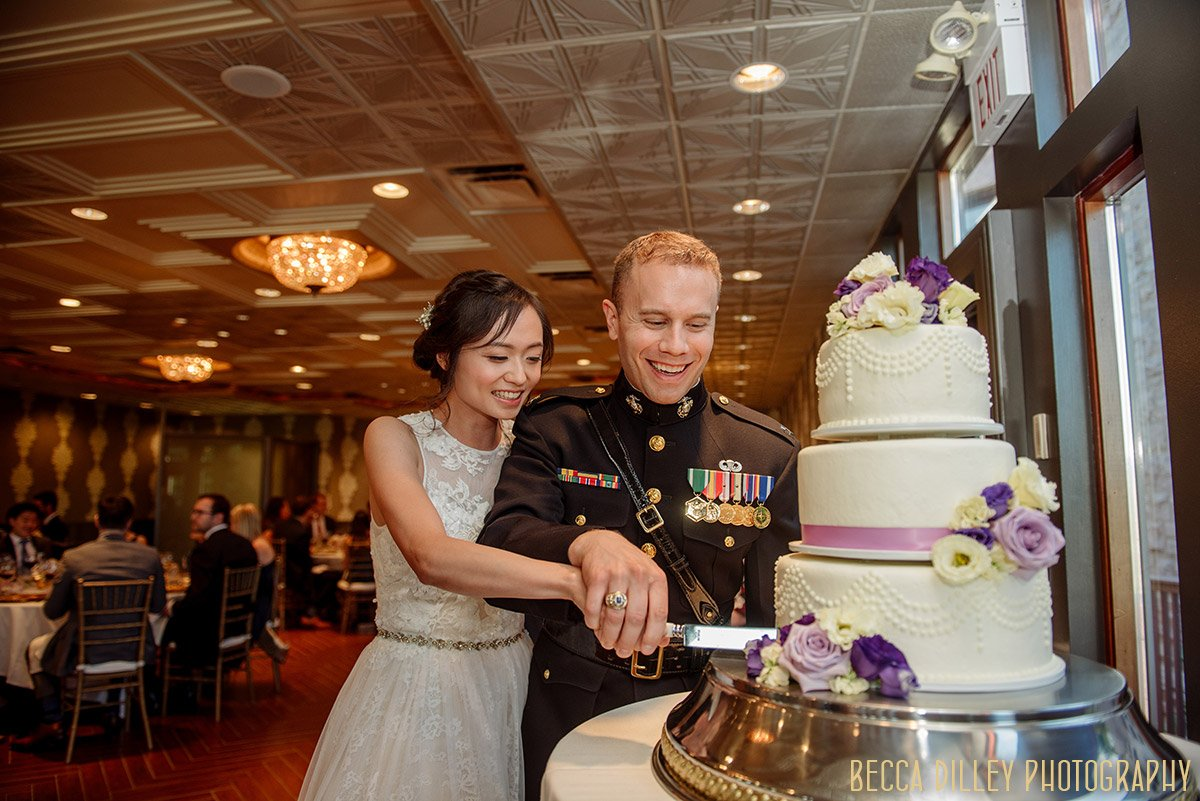 bride and groom cut cake with military knife at minneapolis mansion wedding