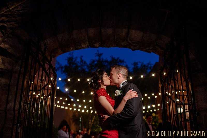 bride in red dress and groom in military jacket kiss outside van dusen mansion at night after wedding