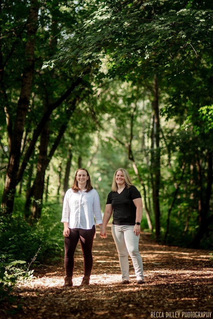 Richardson Nature Center engagement photos two women standing on path in woods