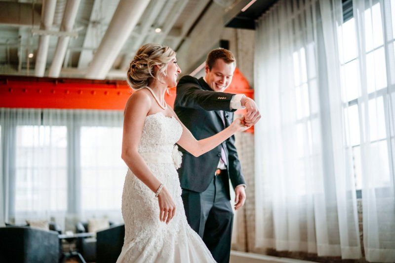 groom twirls around bride before Machine shop wedding