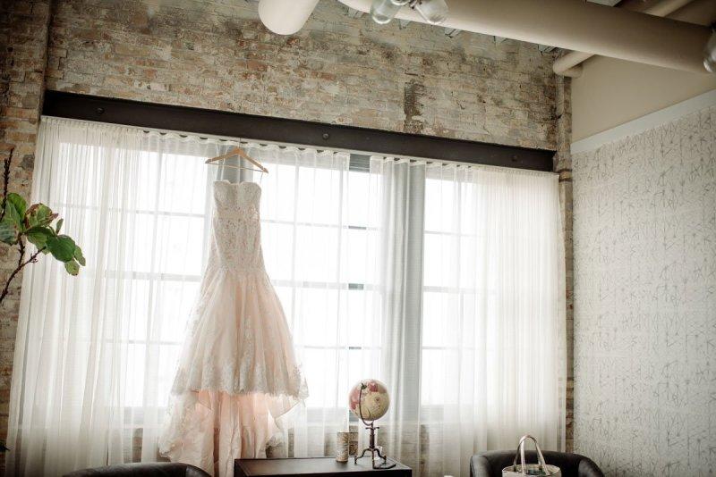 Machine shop wedding dress hanging in window