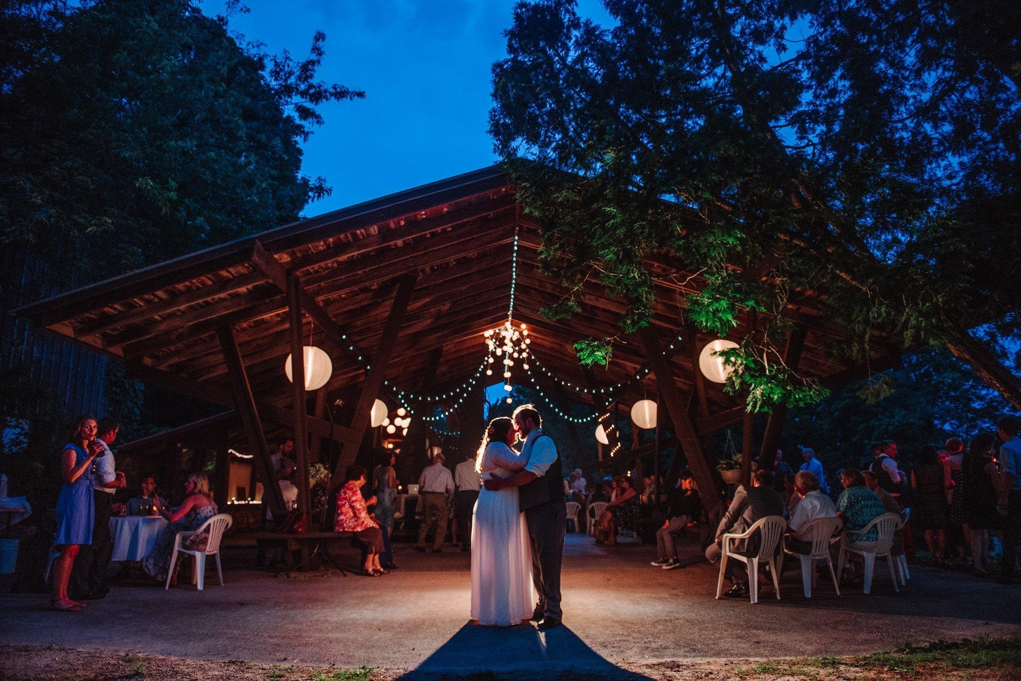 couple outside pavillion hilltop wedding spring green