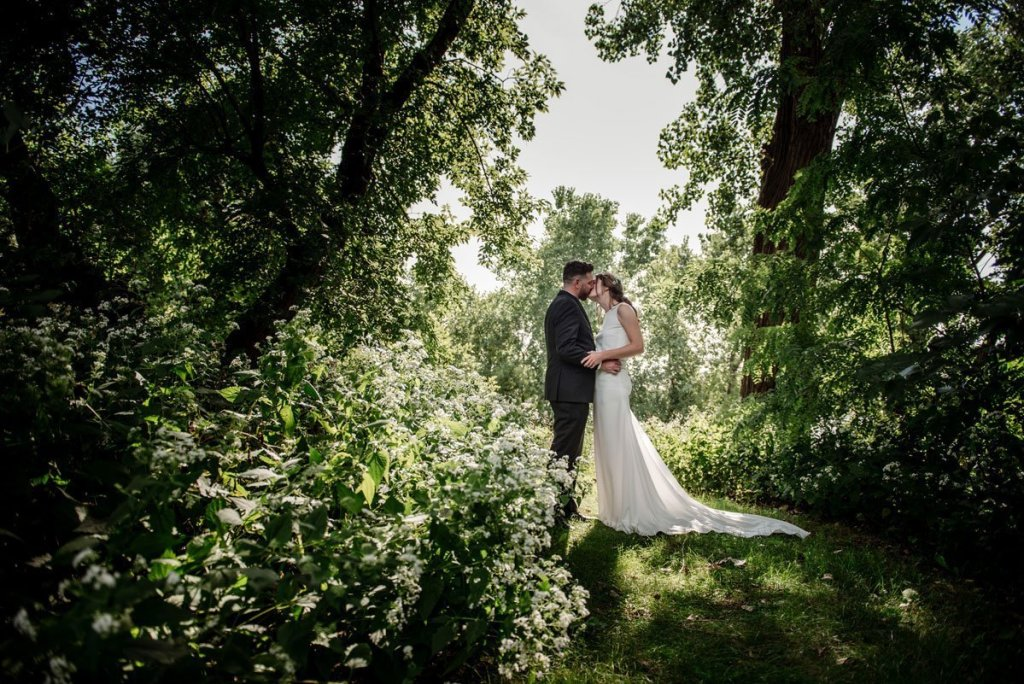 dive bar wedding couple in sunlit trees by minneapolis park after their wedding