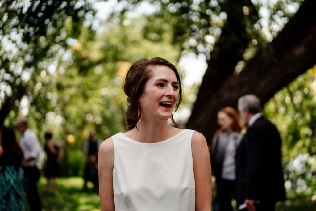mn park wedding in northeast before dive bar wedding reception bride laughing with guests