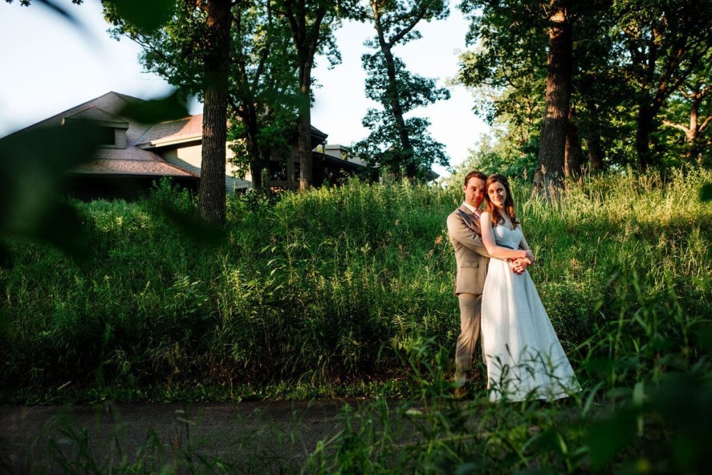 couple with tall grasses and setting sun at silverwood park wedding mn