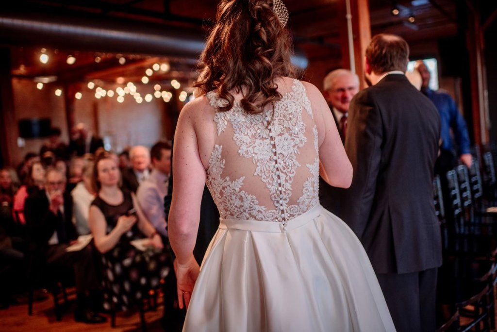 back of bride's lace dress as she enters cocktail hour at solar arts