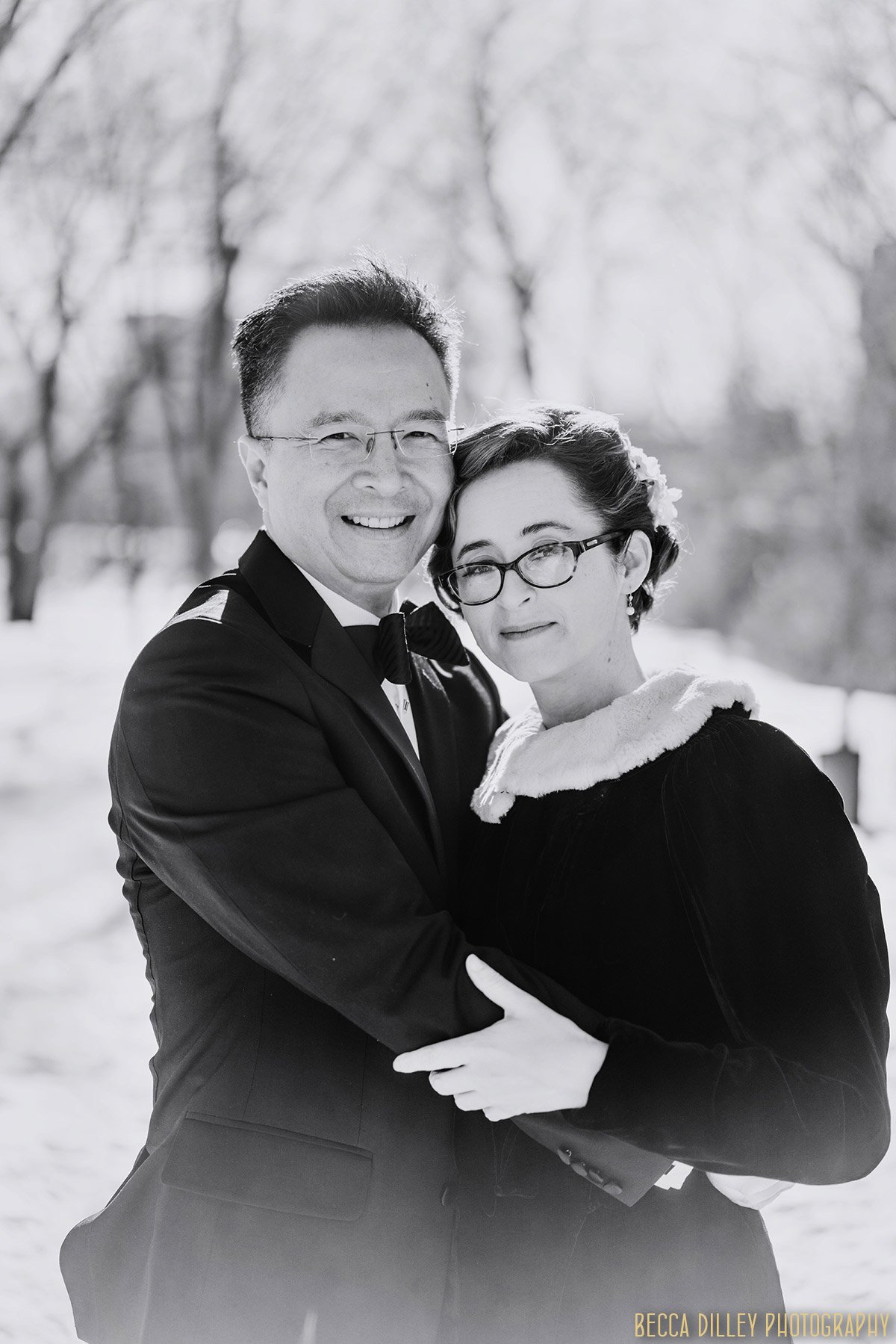 couple embrace on snowy day before winter elopement minneapolis