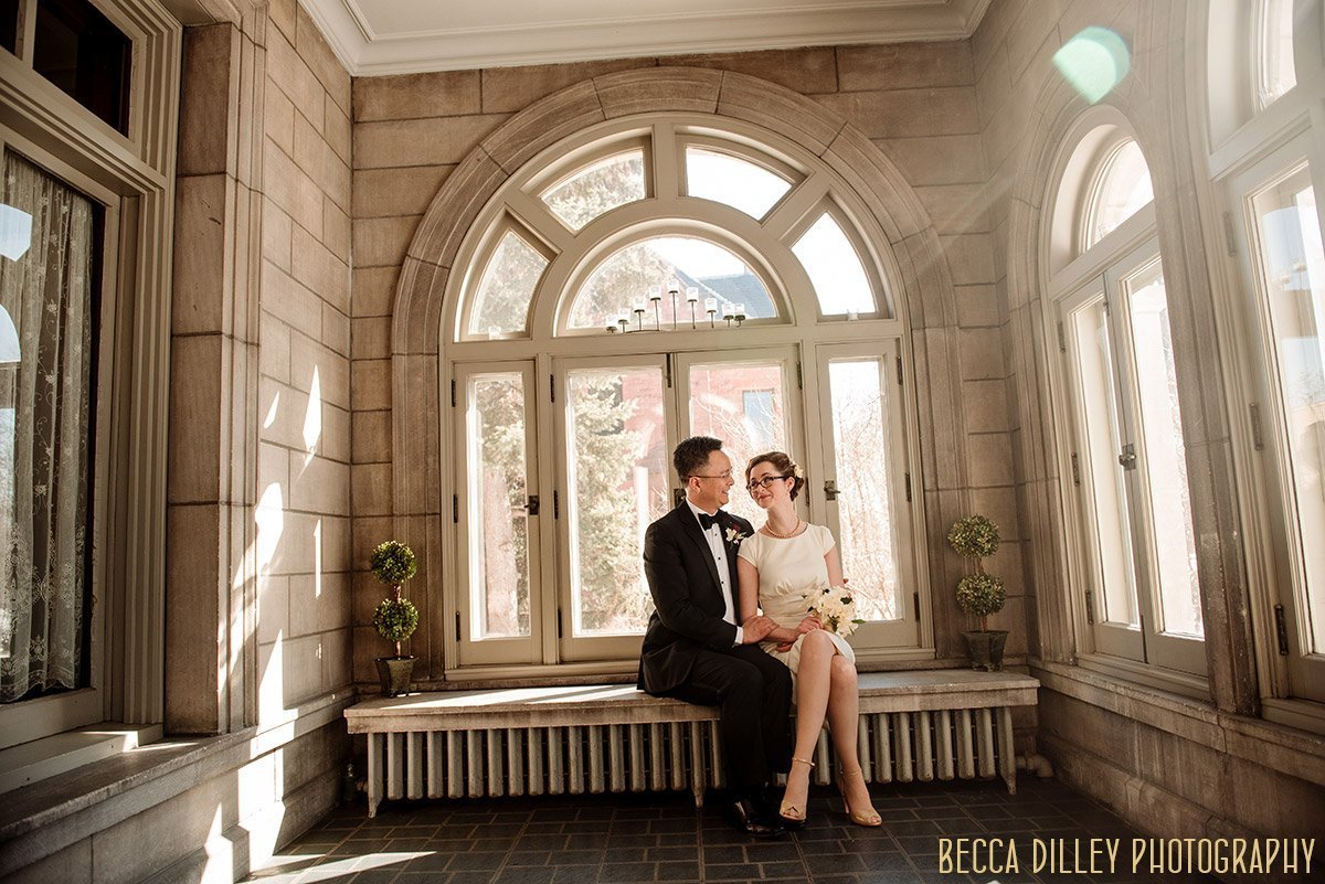 couple on stone bench of solarium in minneapolis mansion before their wedding