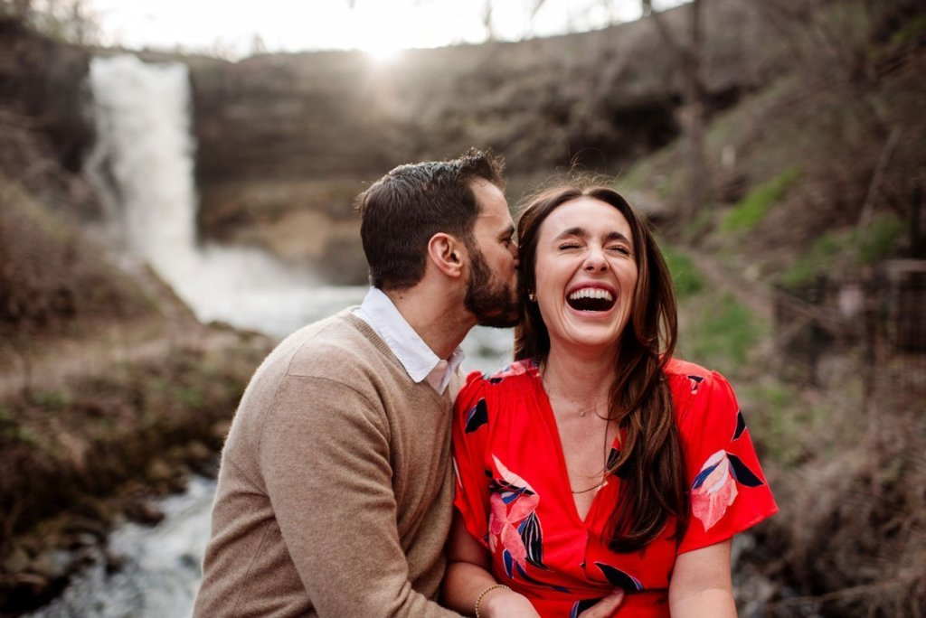 couple laughing with minnehaha falls behind them in summer