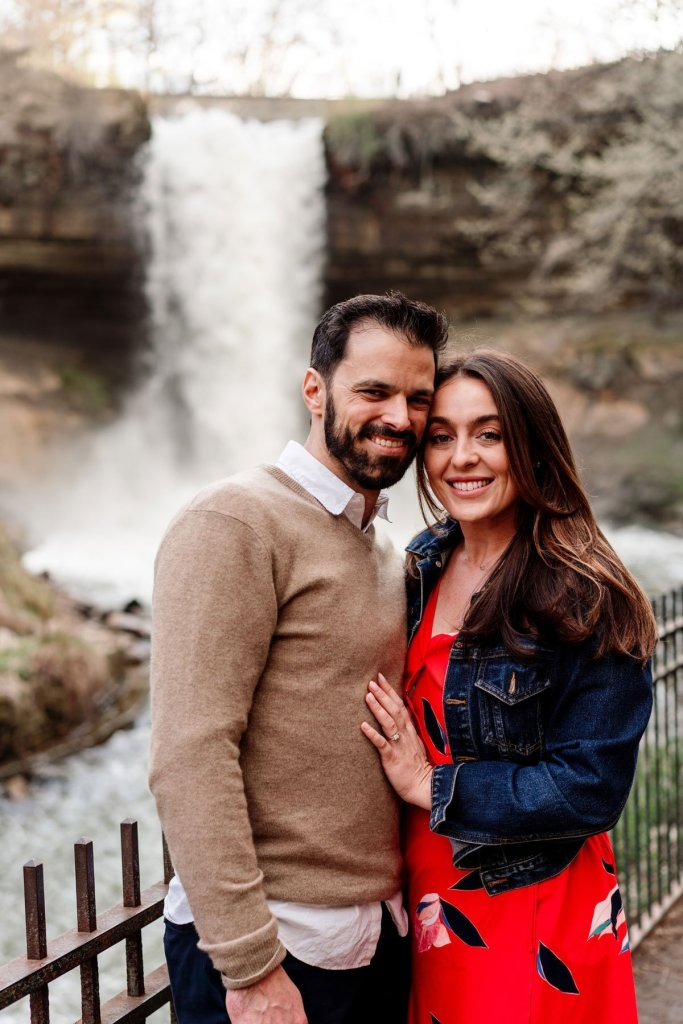 jean jacket couple having fun at minnehaha falls for portraits by the waterfall in minneapolis summer