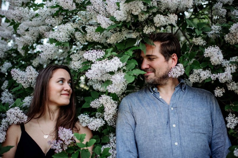 article about having happy engagement photos featuring portrait of couple surrounded by lilac bush in minneapolis