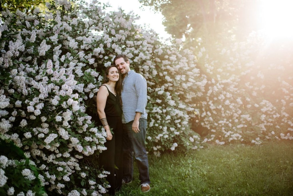 sunlight behind couple at blooming lilac bush in minneapolis