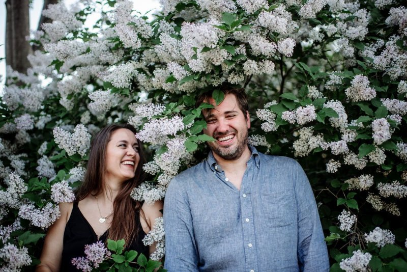 happy engagement photos with this funny portrait of couple inside a lilac bush with blooms around their faces