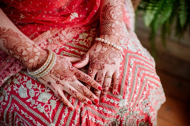 brides hands covered in mehndi henna before her wedding. her hands rest on a red sari.