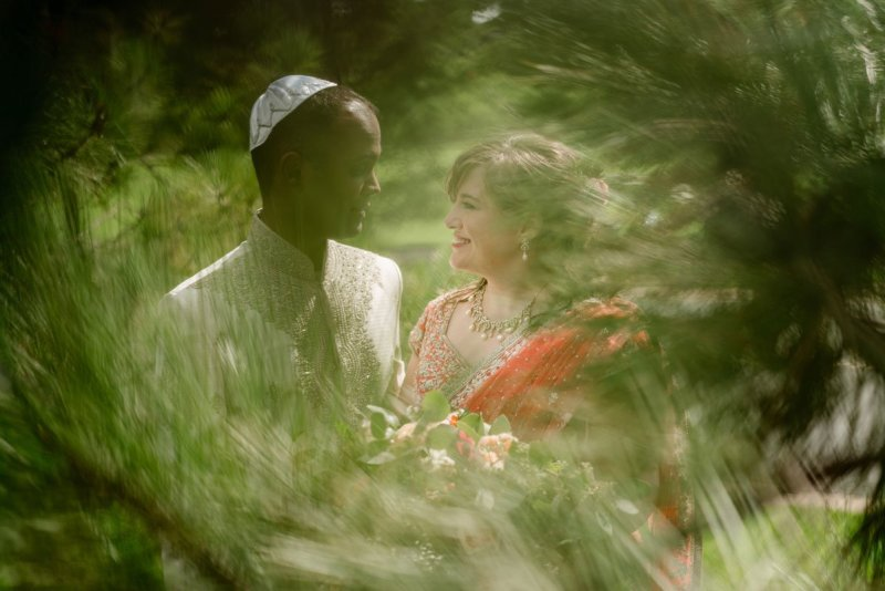bride and groom partially obscured behind pine trees before their hindu jewish wedding ceremony